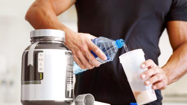 Kraftsportler bereitet sich einen Proteindrink zu