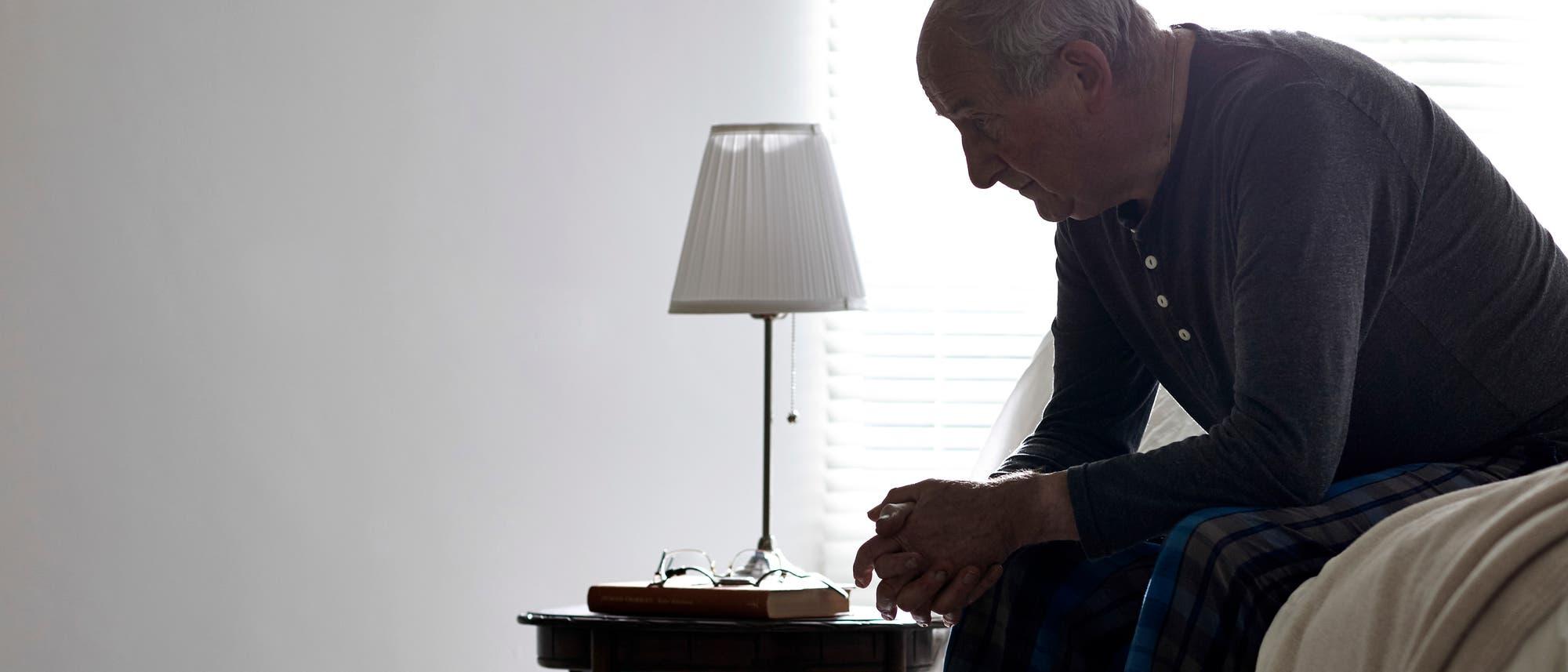 Ein Mann sitzt gekrümmt auf dem Sofa