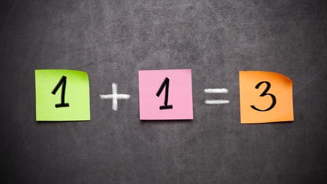 Auf drei bunten post-its steht die Formel 1 + 1 = 3.