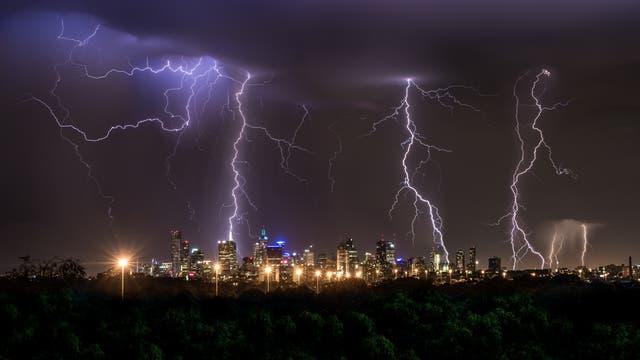 Gewitterblitze über der nächtlich erleuchteten Großstadt Melbourne.