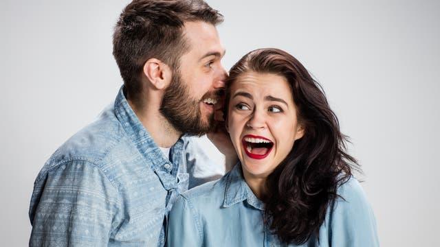 Mann spricht Frau etwas ins Ohr, sie lacht ekstatisch