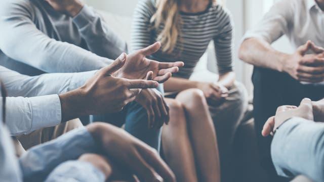 Eine Gruppe Menschen sitzt zusammen und diskutiert