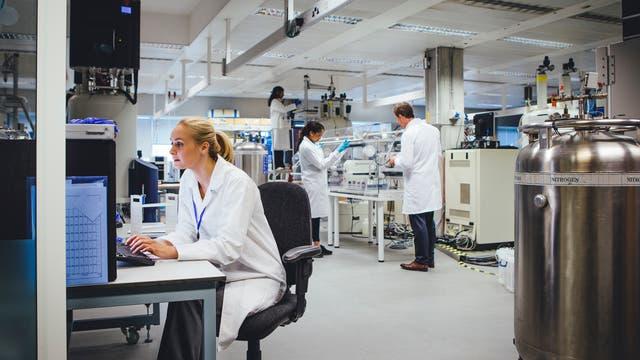 Eine gruppe von Fachleuten in einem Labor, das für medizinisch-pharmazeutische Forschung ausgestattet ist.