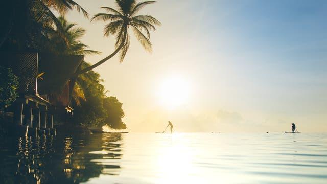 Urlaubsidyll mit Stehpaddlern im Sonnenuntergang