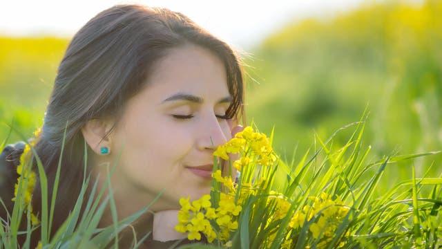 Eine junge Frau riecht an gelben Blumen.