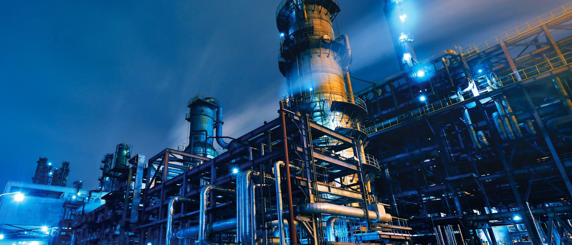 Ein blau erleuchtetes Raffineriegebäude mit vielen Rohrleitungen und dergleichen.