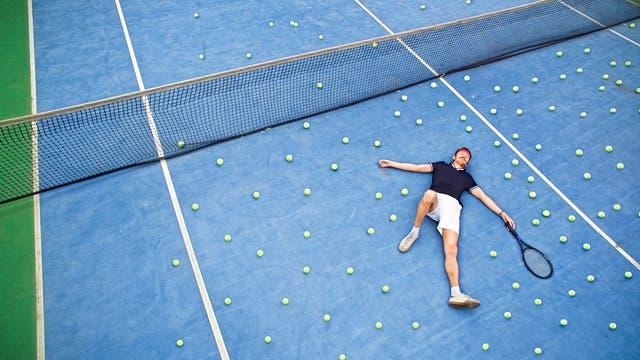 Ein Tennisspieler auf einem blauen Tennisplatz.