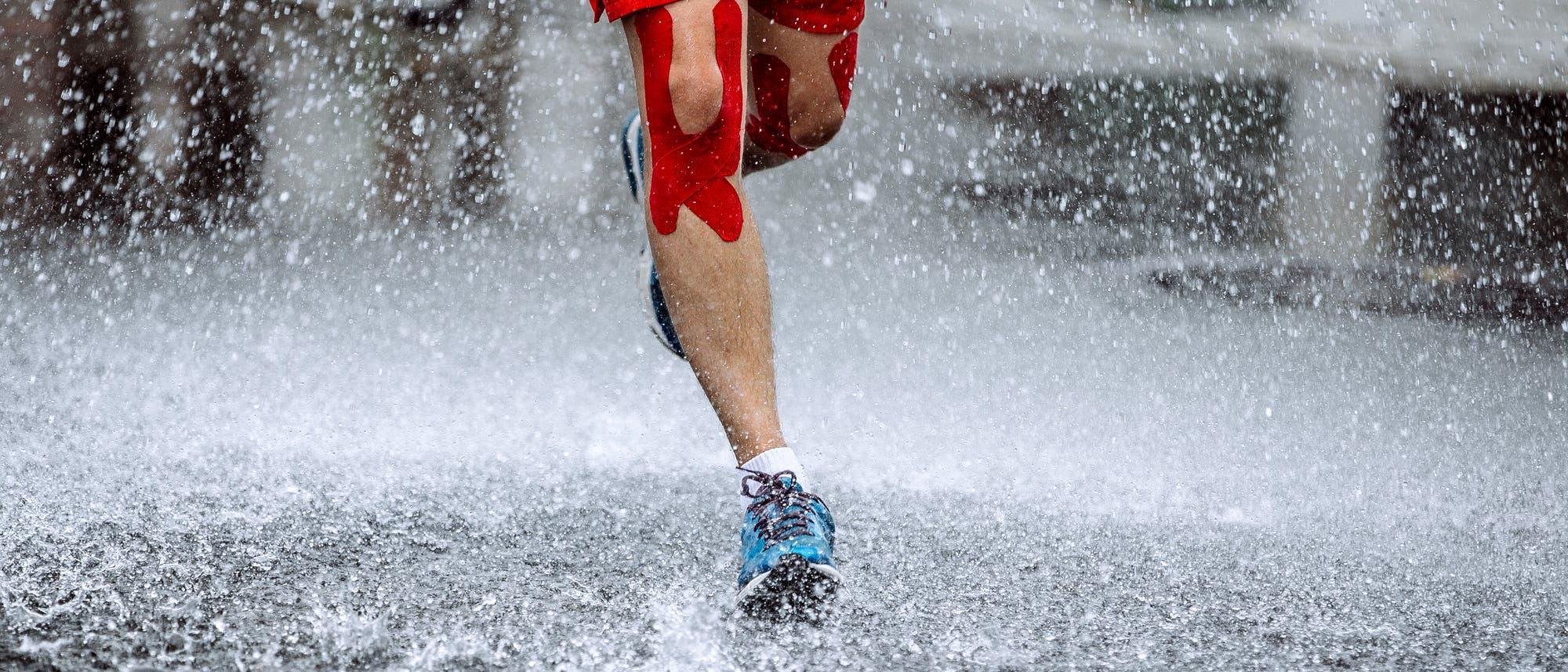 Ein Mann mit Kinesiotapes läuft durch den Regen