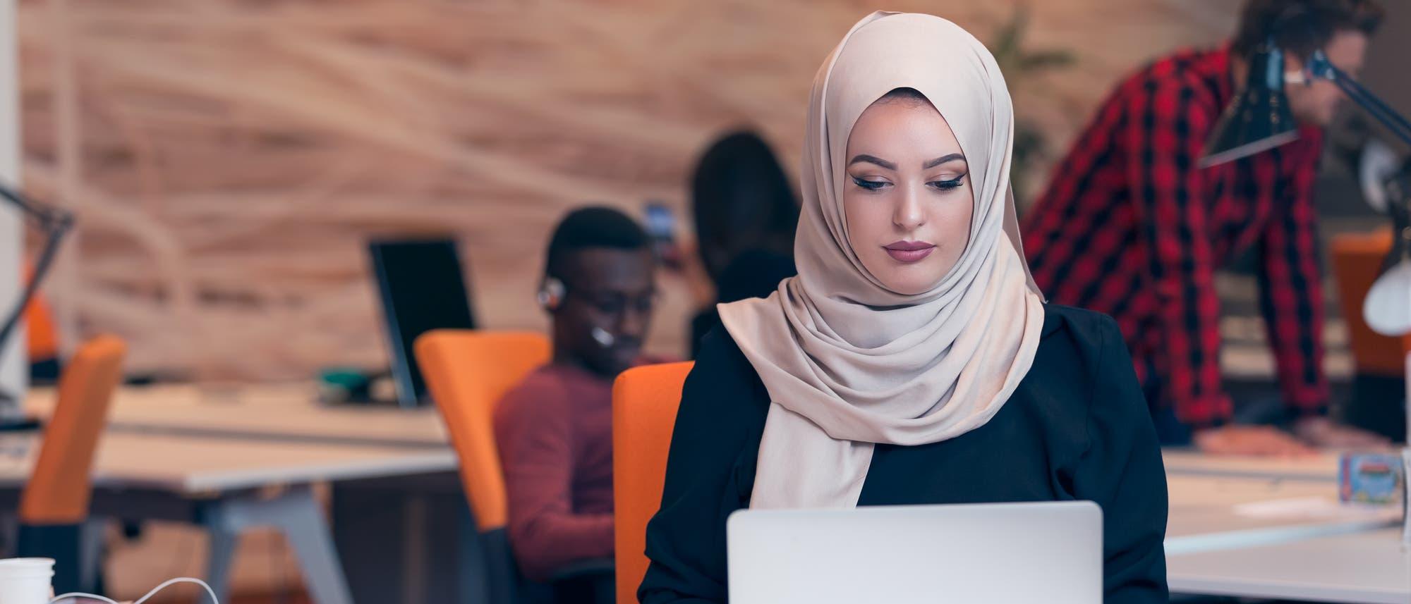 Eine muslimische Frau arbeitet konzentriert am Computer