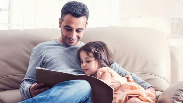 Ein Vater liest seiner Tochter aus einem Buch vor