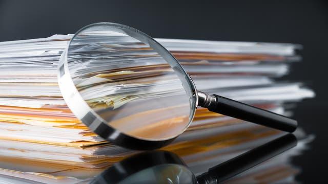 An einen Stapel Dokumente ist eine Lupe gelehnt.