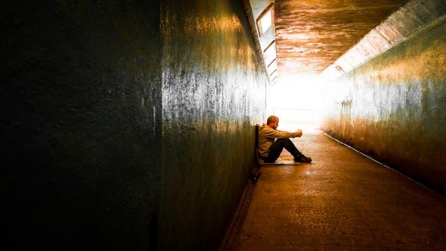 Obdachloser junger Mann sitzt in Unterführung