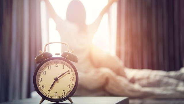 Frau streckt sich beim Aufstehen, der Wecker zeigt kurz nach sieben