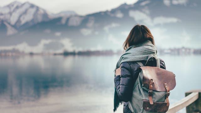 Frau blickt auf eine winterliche Seenlandschaft