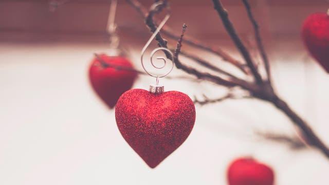 Herzförmige Kugeln hängen an winterlichen Zweigen
