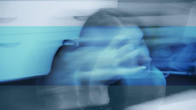 Ein Frau, über der ein verschwommener und blauer Filter liegt, fasst sich ins Gesicht.