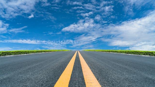 Eine Straße mit zwei Gelben Linien in der Mitte zieht sich zum Horizont.