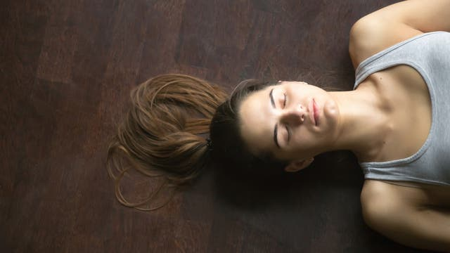 Kopf einer Frau, die mit geschlossenen Augen auf dem Boden liegt