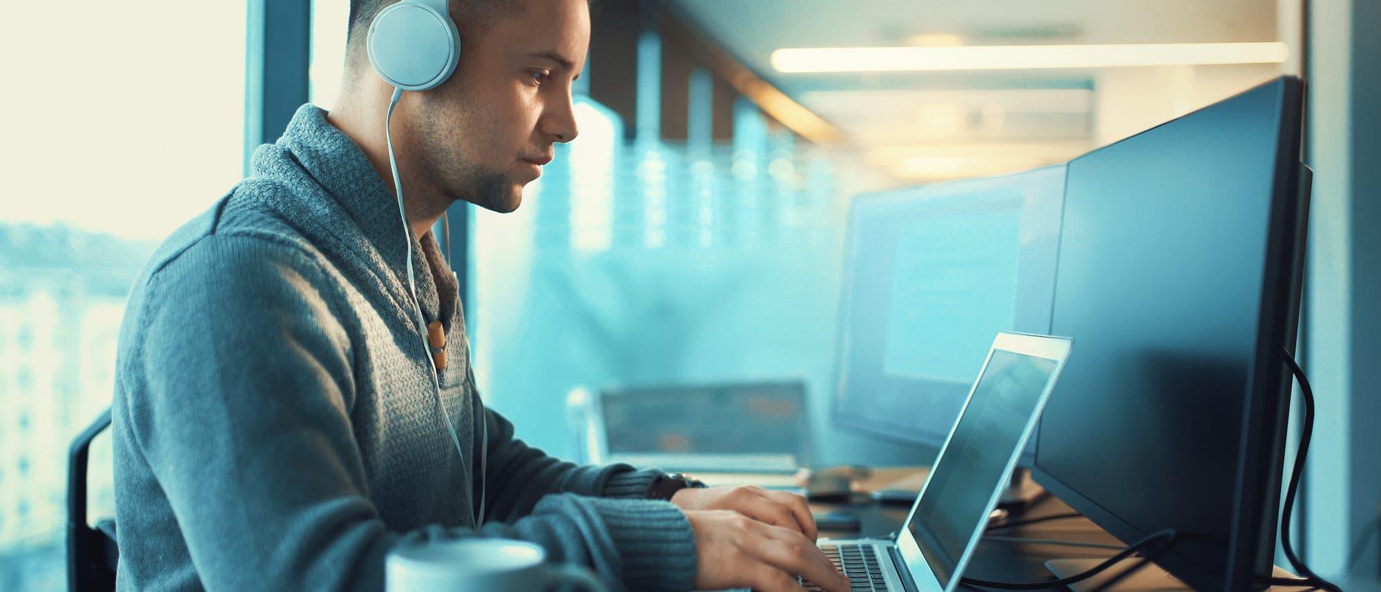 Mann mit Kopfhörer am Laptop