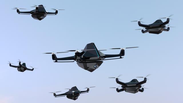 Mehrere bedrohlich aussehende Quadcopter-Drohnen vor blauem Himmelshintergrund.