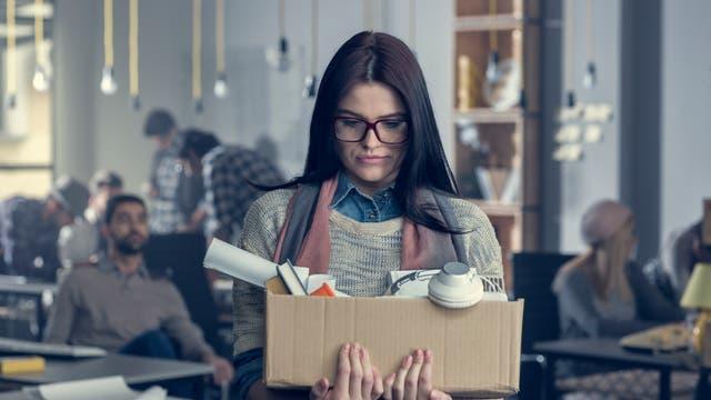 Junge Frau trägt einen Karton mit ihren Habseligkeiten aus dem Büro.