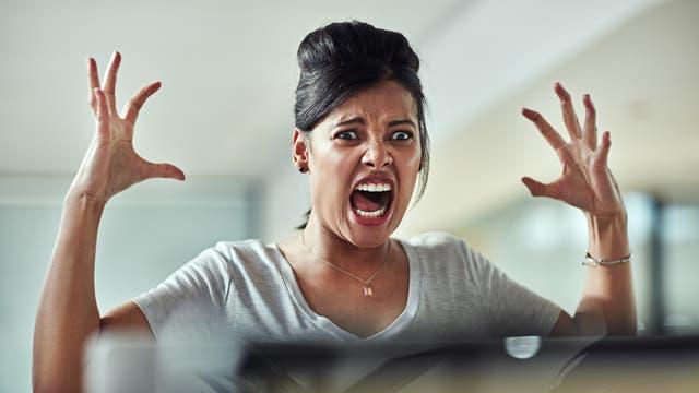 Frau sitzt vor Computer an einem Schreibtisch und schreit vor Entsetzen, nachdem sie unvorsichtigerweise Facebook-Kommentare gelesen hat.