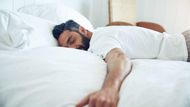 Ein Mann liegt zufrieden mit ausgebreiteten Armen bäuchlings auf einem Bett.