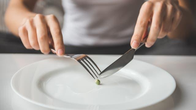 Eine Frau isst eine einzelne Erbse mit Messer und Gabel.