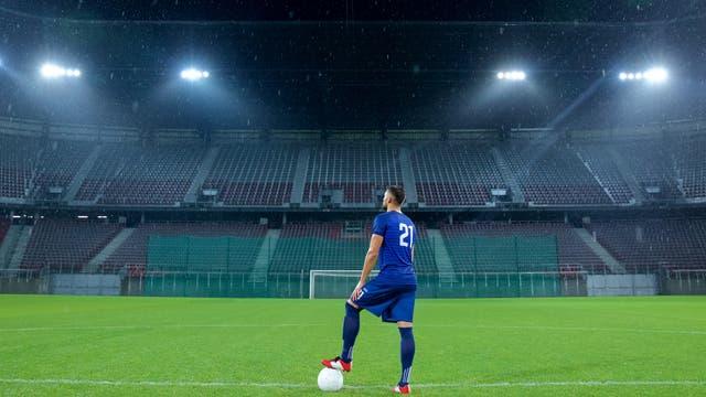 Ein Fußballer steht allein in einem leeren Stadion