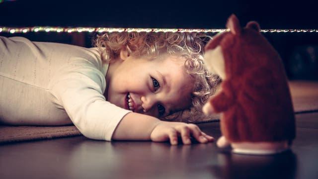 Kind versucht, Stoffhamster unter dem Bett hervorzuholen