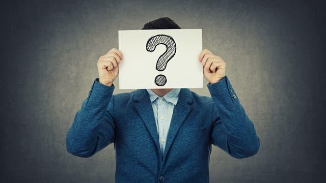 Ein Mann hält ein Schild mit einem Fragezeichen vor seinen Kopf.