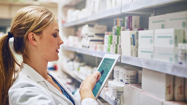 Eine Ärztin steht mit einem Tablet vor einem Medikamentenregal.