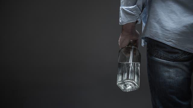 Mann mit Schnapsflasche in der Linken