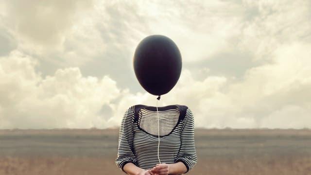 Ein Frau ohne Kopf hält einen schwarzen Luftballon in der Hand.
