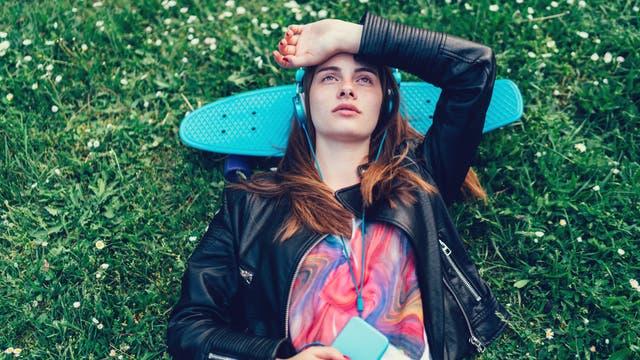 Jugendliche liegt im Gras und hört Musik