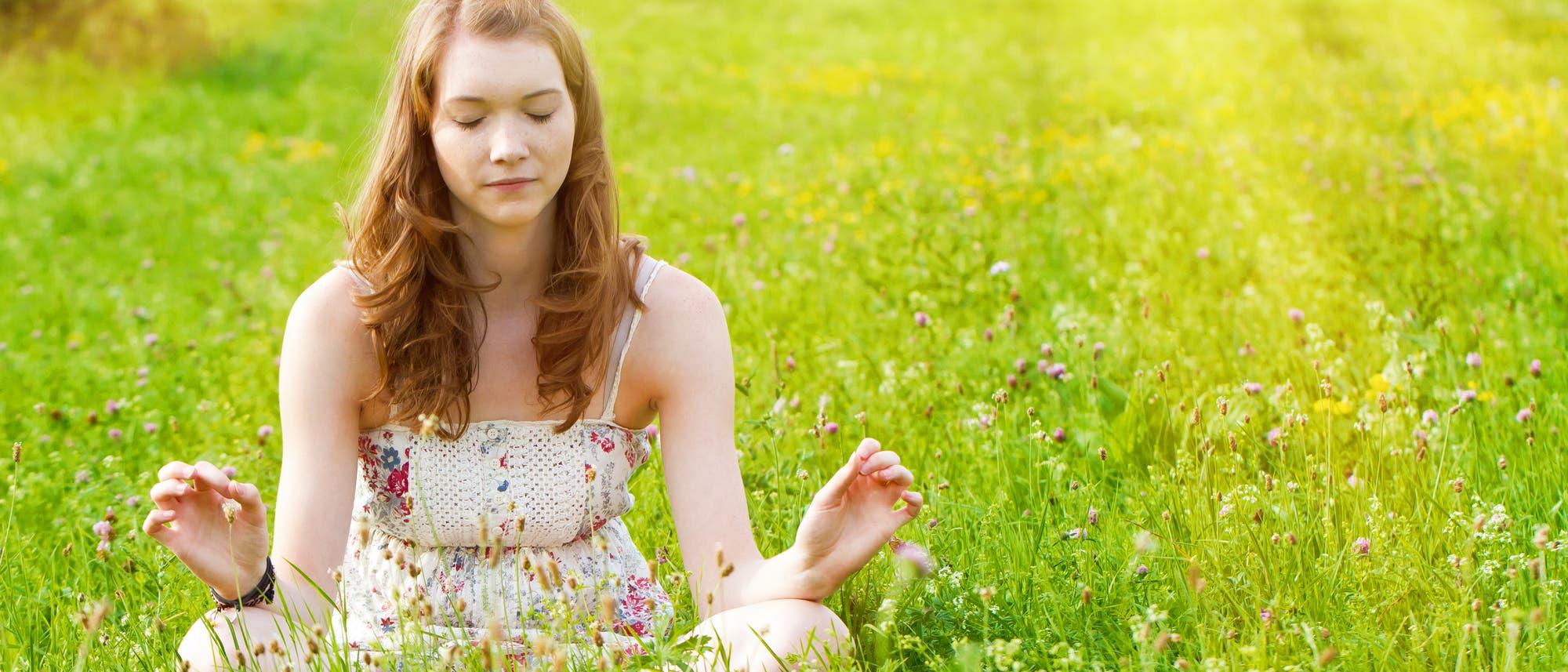 Jugendliche meditiert auf Wiese
