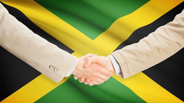 Handschlag vor der Jamaikaflagge