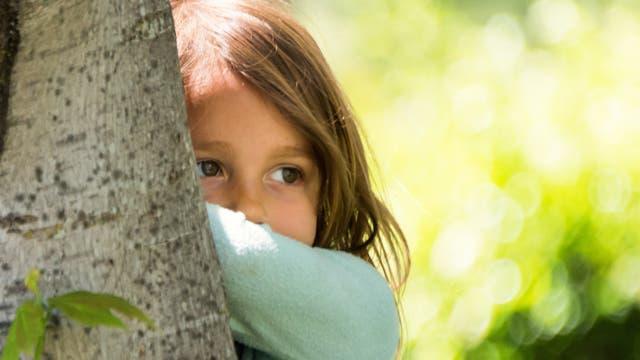 Ein kleines Mädchen steht hinter einem Baum und guckt etwas traurig
