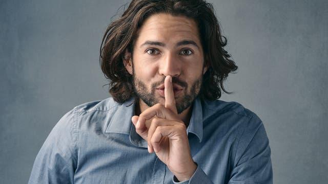 Ein Mann hält verschwörerisch einen Finger über den Mund.