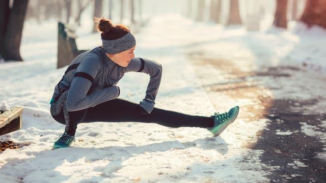 Eine Joggerin dehnt sich auf einem verschneiten Weg