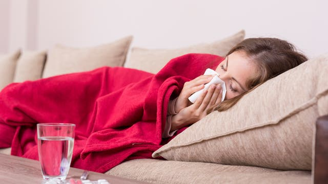 Eine Frau liegt krank im Bett und schneuzt sich.