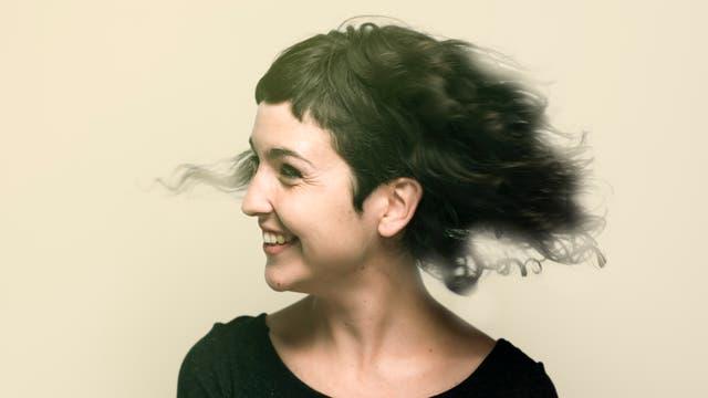 Eine fröhliche Frau mit lustigem Lockenkopf im Profil