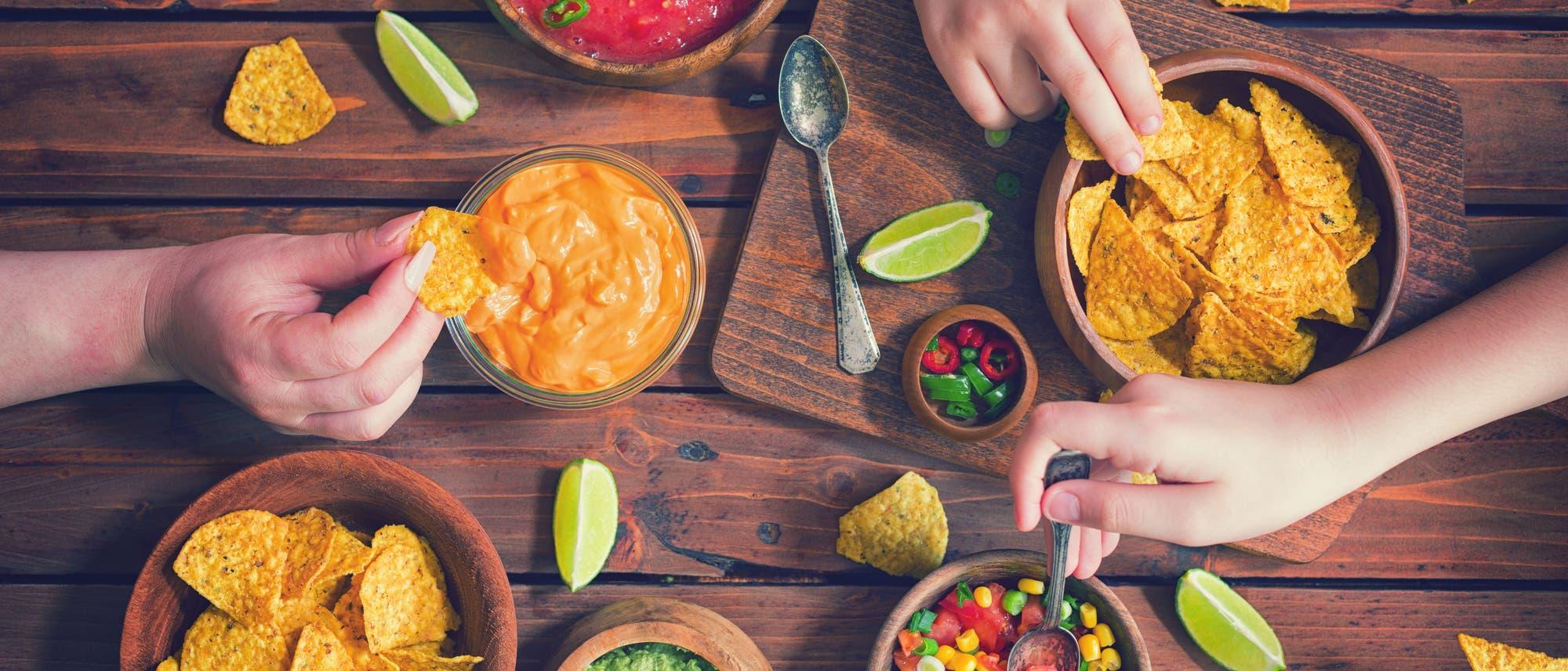 Drei Hände greifen nach Snacks auf einem Tisch