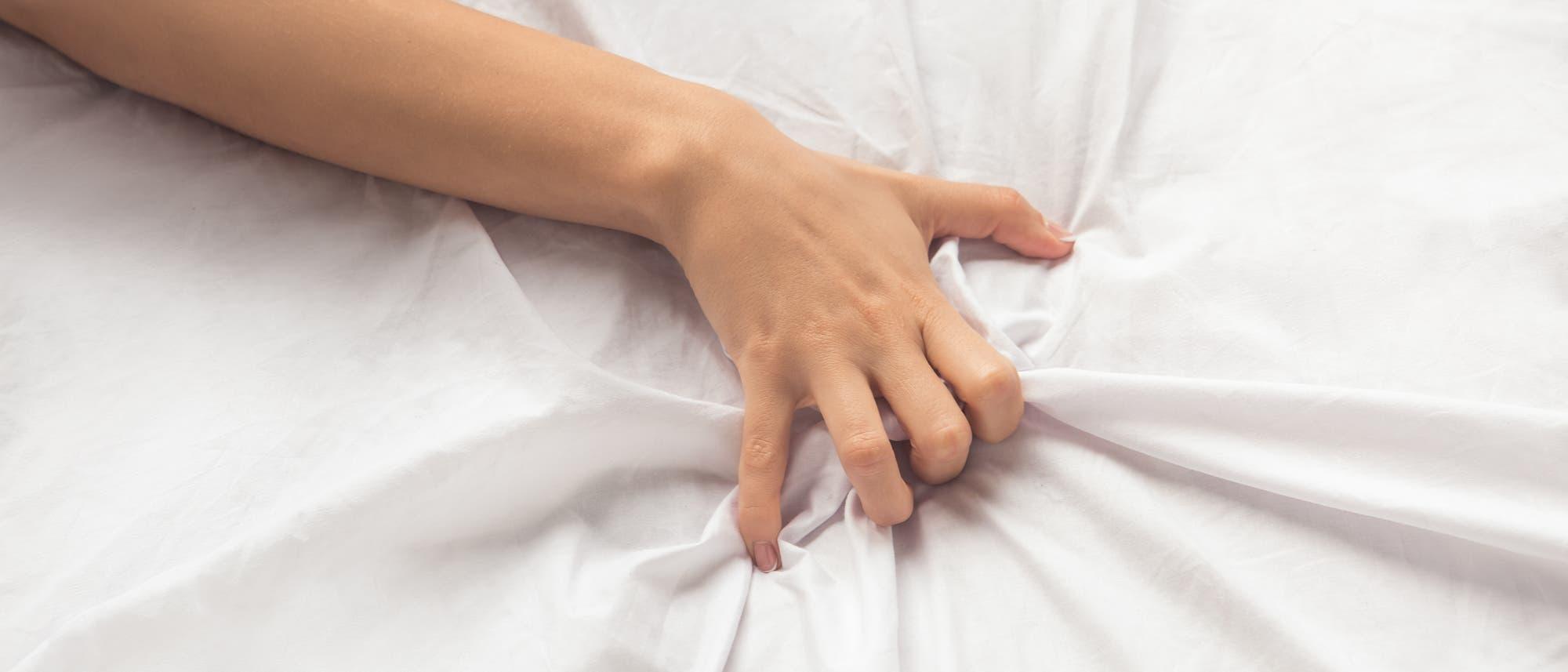 Hand krallt sich ins Bettlaken
