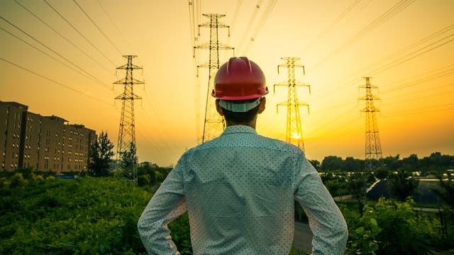 Ingenieur vor Strommasten