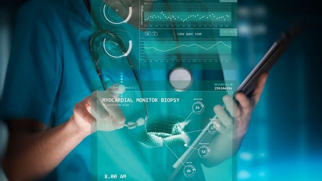 Eine Ärztin in Berufskleidung arbeitet an einem virtuellen, innovativen medizinisches Monitoringgerät