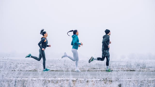 Drei junge Leute joggen in winterlicher Landschaft