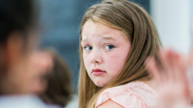 Eine junge Schülerin dreht sich im Klassenzimmer um.