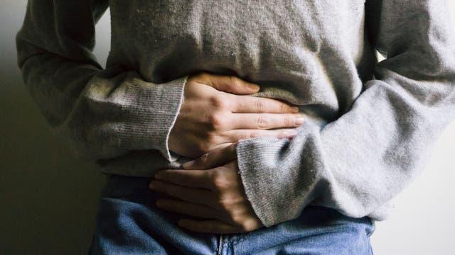 Eine Frau hält sich mit beiden Händen den Bauch