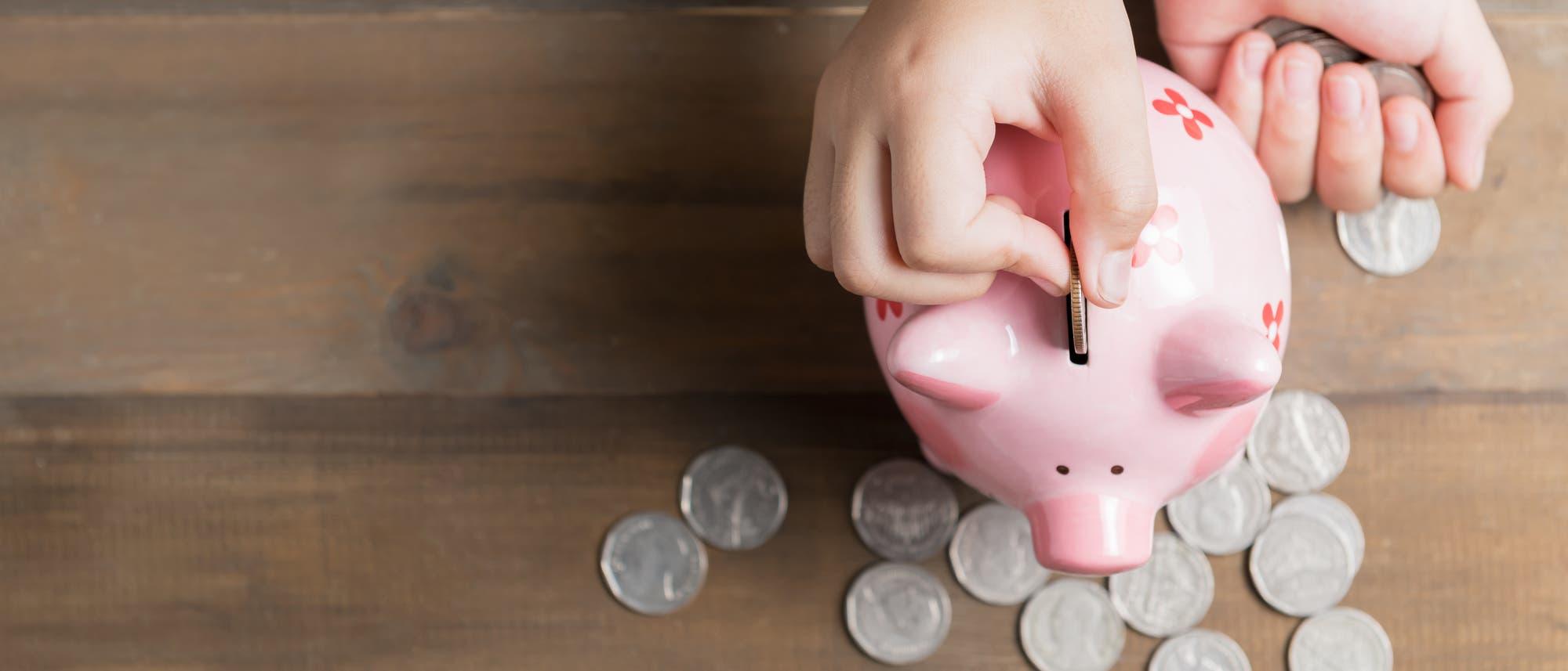 Kinderhand mit Münzen und Sparschwein